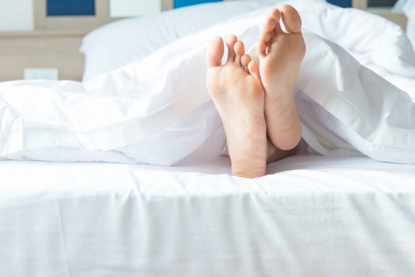 close up of woman's feet sticking out from bed cover