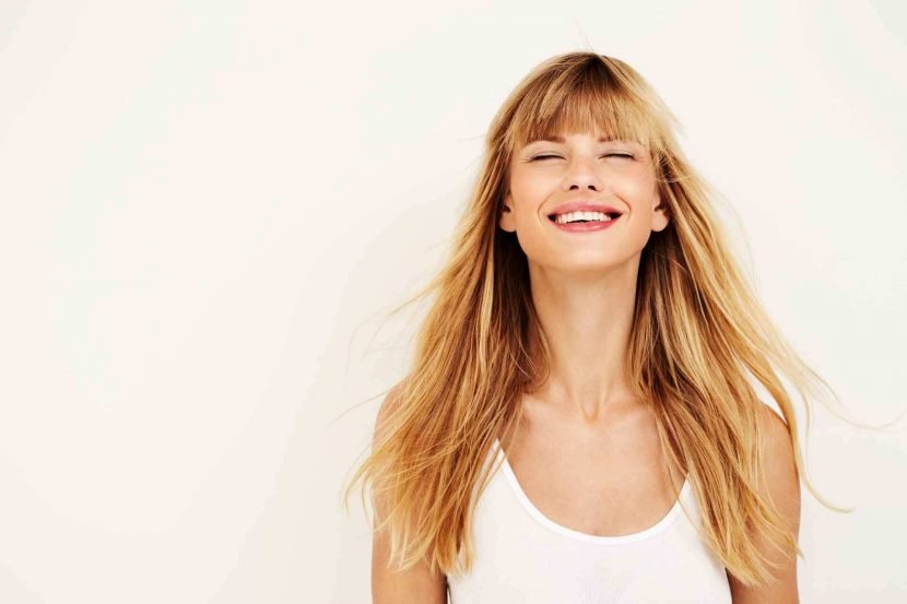 happy woman with long blonde hair on white background